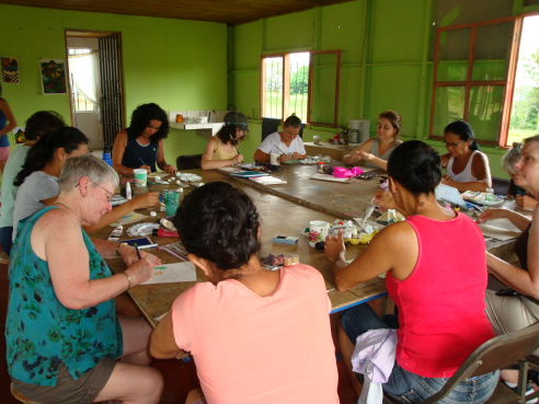 Explore & Create group participating in a round robin painting exercise with painting group Corazones Valientes